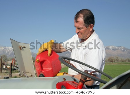 senior aged man filling a tractor gas tank with gas from gas can - stock photo