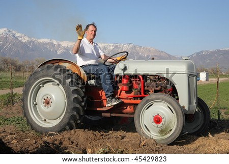 senior aged man riding on a farm tractor and waving to camera