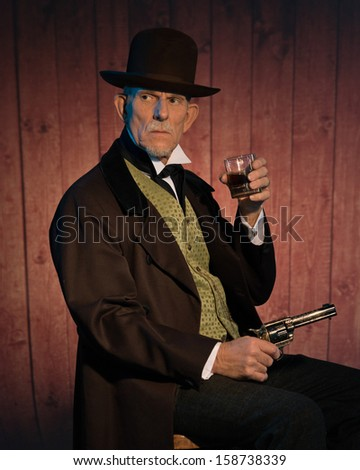 Senior alert western man wearing a brown hat and coat holding a revolver gun and whiskey. Sitting on chair in front of wooden wall in saloon. - stock photo