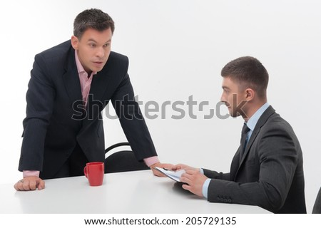 Senior and junior business people discuss something during their meeting, boss stands above employee holding clipboard isolated on white background