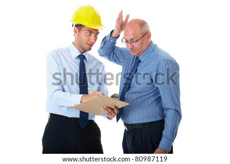 senior and junior businessman discuss and argue over something during their meeting, one of the wear yellow hardhat, isolated on white - stock photo