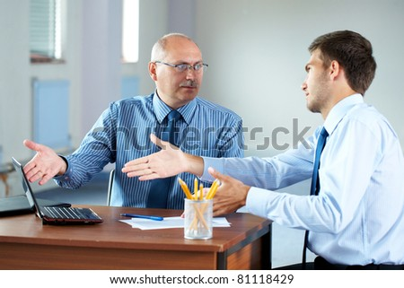 senior and junior businessman discuss something during their meeting - stock photo