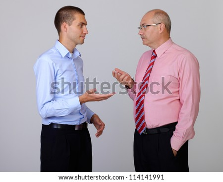 Senior and junior businessman discuss something during their meeting, isolated on grey
