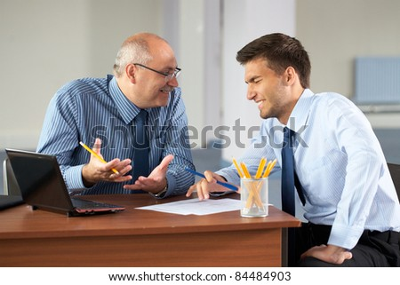 senior and junior businessman discuss something during their meeting, joking about somethign and both laugh, office background - stock photo