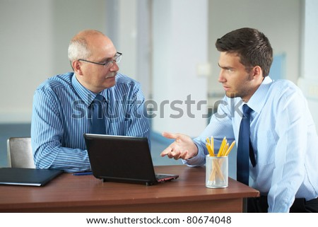 senior and junior businessman discuss something during their meeting, office background - stock photo