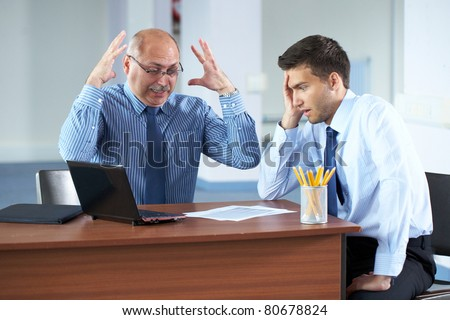 senior and junior businessman discuss something during their meeting, office background, stress, shock concept - stock photo