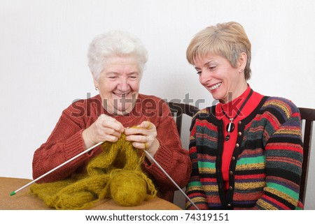 Senior and mature womans speaking  laughing  and learning knitting - stock photo