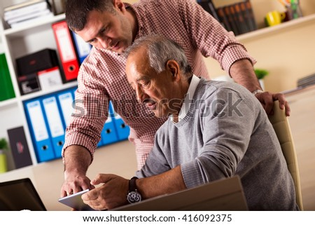 Senior and young businessman working together on a project in the office, they are looking something on tablet.
