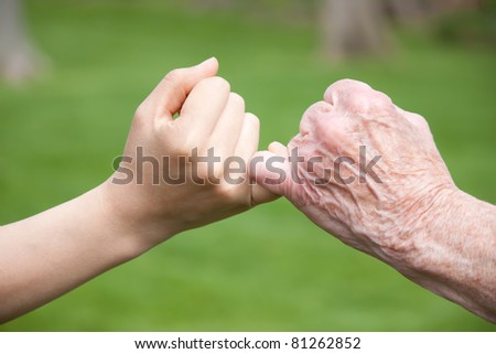 Senior and Young Hands Promise - stock photo