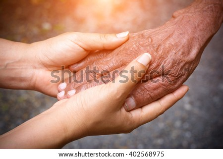 Senior and young holding hands and color tone effect - stock photo