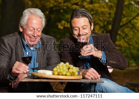 Senior and young man enjoying red wine and cheese outdoors in autumn forest. - stock photo