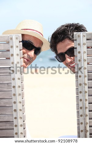 senior and young man relaxing on beach - stock photo