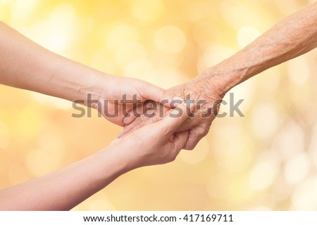 Senior and young women holding hands on abstract nature background. - stock photo