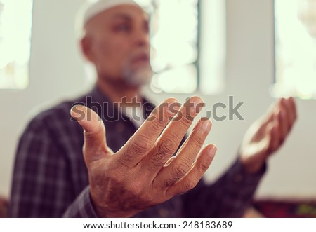 Senior Arabic Pakistani man praying in mosque - stock photo