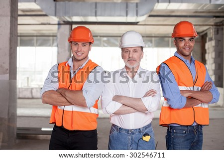 Senior architect and his colleagues are standing and crossing their arms. They are looking at the camera confidently and smiling. The men are building new construction - stock photo