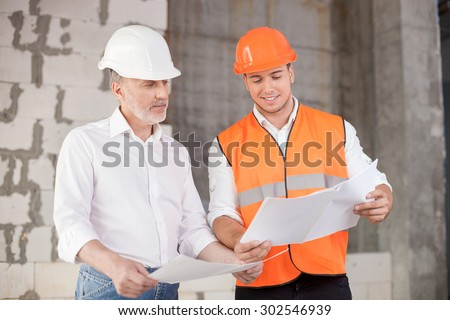 Senior architect and young builder are discussing the new project. They are holding blueprints and looking at it with interest. The foreman is smiling - stock photo