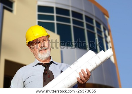 Senior architect at the site with blueprints
