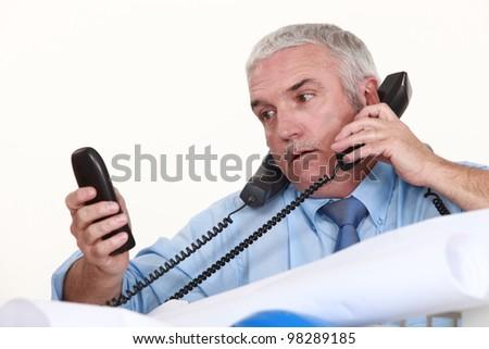senior architect getting multiple calls - stock photo