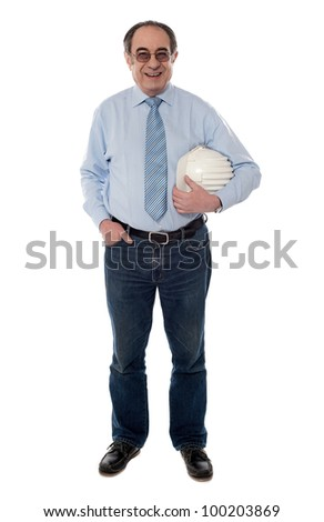Senior architect holding helmet in one hand, full length view - stock photo
