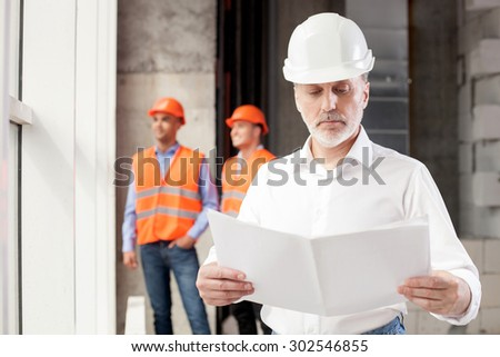 Senior architect is planning to build a new construction with his team. He is holding a blueprint and looking at it with concentration. The builders are standing behind him and smiling - stock photo