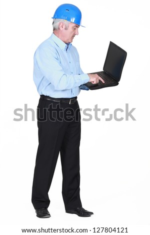 Senior architect typing on laptop - stock photo