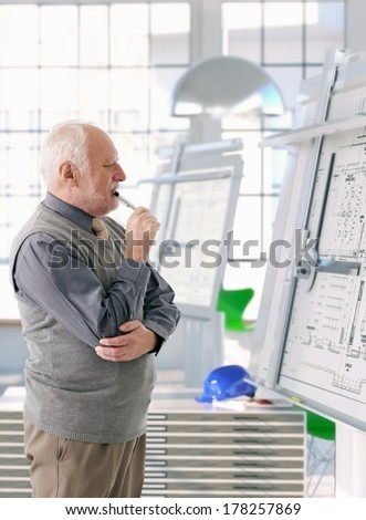 Senior architect working at drawing board, thinking. - stock photo