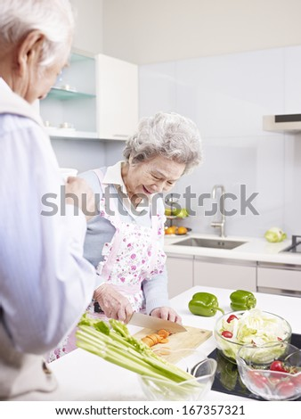 senior asian couple preparing meal together in kitchen. - stock photo