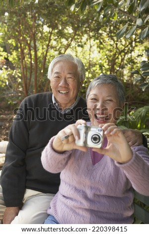 Senior Asian couple sitting on a park bench with a digital camera - stock photo
