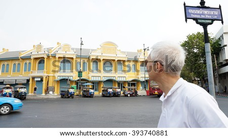 Senior Asian guy in front of Classic Thai architecture at na phra lan road in Bangkok, Thailand - stock photo