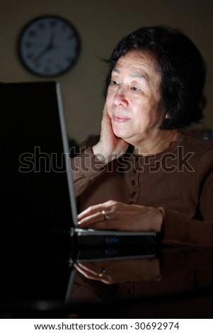 senior asian lady surfing the net late night - stock photo