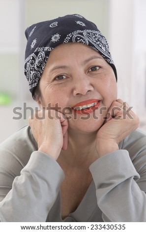 Senior Asian Thai woman wearing headscarff recovering from cancer - stock photo
