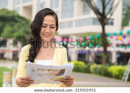 Senior Asian woman reading fresh newspaper outdoors