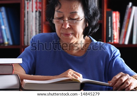 Senior Asian Woman reading in the library - stock photo