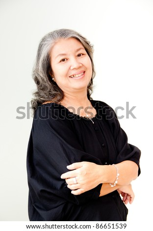 senior asian woman smiling with arms folded - stock photo