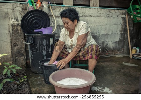 Senior asian woman washing cloths by hand - stock photo