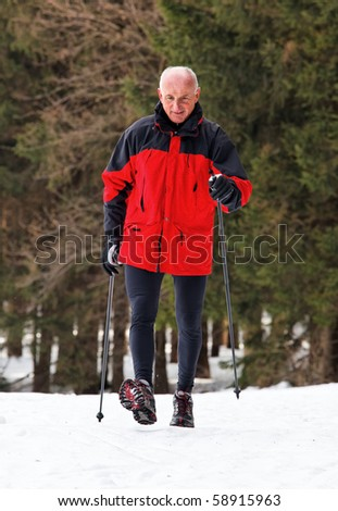 Senior at the snow in winter nordic walking