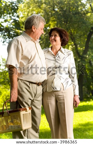 Senior attractive happy smiling couple walking in park, man carrying picnic basket