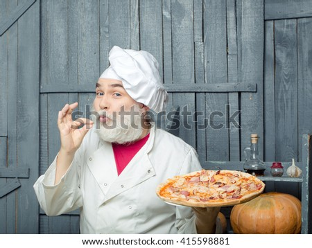 Senior bearded chef with pizza in white uniform with funny face and hat on wooden background