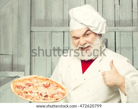 Senior bearded chef with pizza in white uniform with winking face and thumb up on wooden background