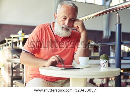 senior bearded man having coffee break and using tablet pc in cafe - stock photo