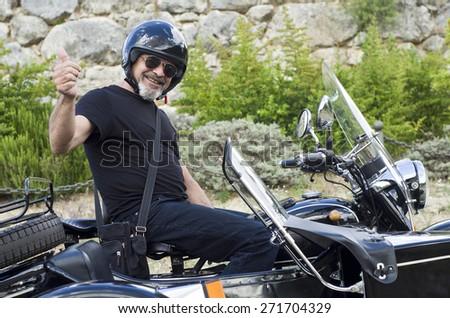 Senior biker at custom doing ok symbol - stock photo