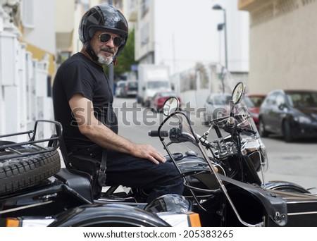 Senior biker on sidecar motorcycle - stock photo