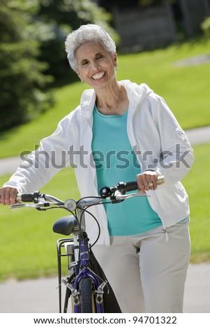 Senior black woman walking her bike through the park - stock photo