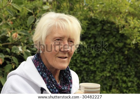 Senior Blonde Woman stops for tea from her gardening