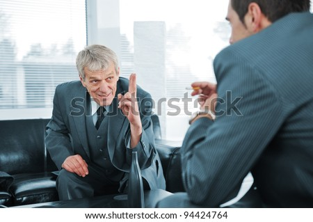 Senior boss giving orders to young colleague at break in office, relaxed meeting - stock photo