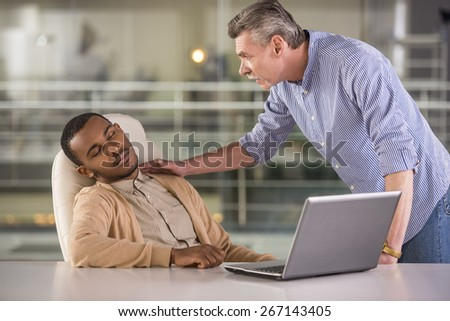 Senior boss waking sleeping young african worker in office. - stock photo