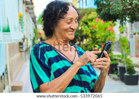 Senior brazillian reading a message on smartphone