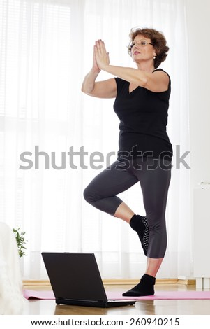 Senior brown haired woman  standing  and  exercising yoga at home. - stock photo