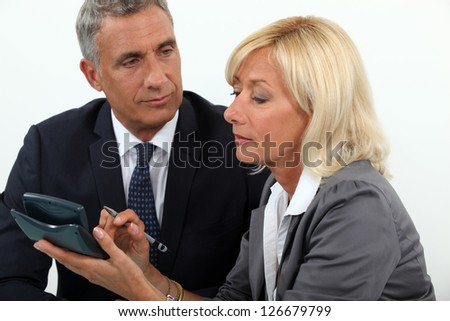 Senior business couple going over finances - stock photo