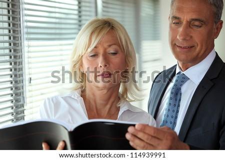 Senior business couple reading through document - stock photo